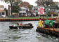 Contractors from Abhe & Svoboda Inc. approach a barge along the Point Pleasant Canal bulkhead during a repair project. On both sides of the canal, the steel sheet-pile bulkhead protects development. The U.S. Army Corps of Engineers Philadelphia District is working to repair the bulkhead with innovative techniques rather than replace it.
